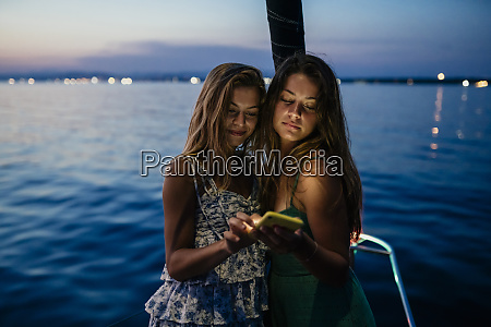 friends on sailboat sharing text message