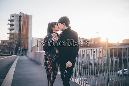 trendy couple kissing on bridge milan