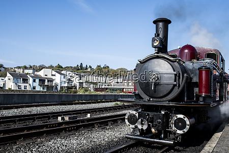 steam train passing through town llanaber