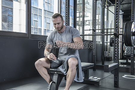 man resting and drinking water at