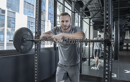 man resting on barbell at gym