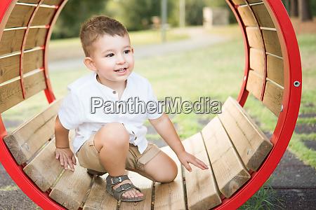 toddler kneeling inside circular swing in