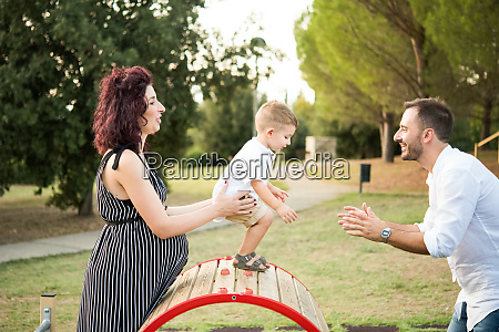 parents playing with son on circular