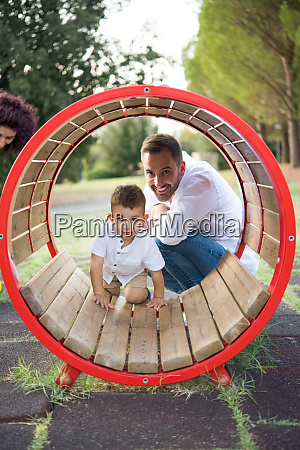 father watching son playing in circular
