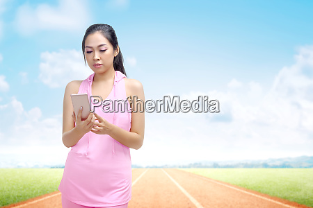 asian runner woman using a mobile
