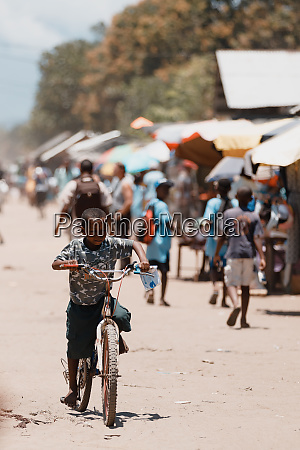 young boy riding bicycle on street