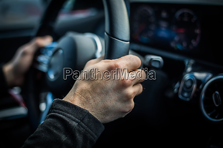 mans hand holding the steering wheel