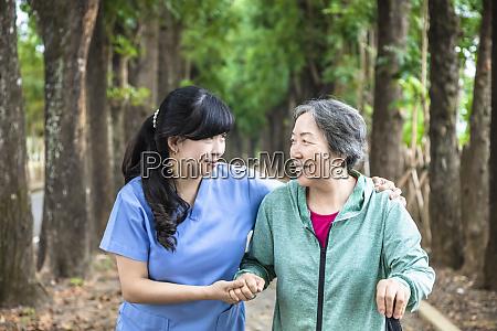 smiling nurse helping senior woman to