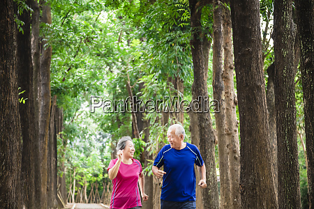 happy asian senior couple jogging together