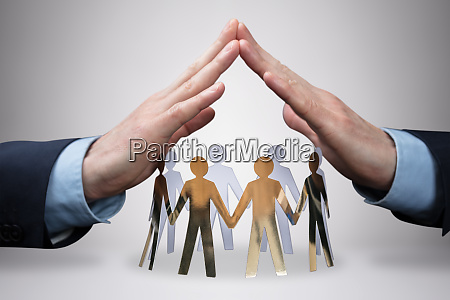 businessmans hand protecting paper cut out