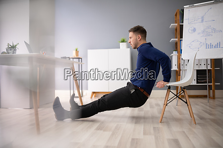 businessman doing triceps dips in office