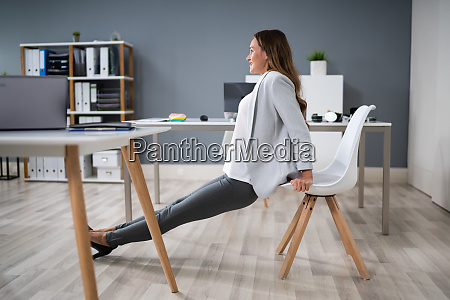 businesswoman doing triceps dips in office
