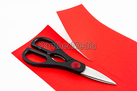 scissors cutting red paper in two