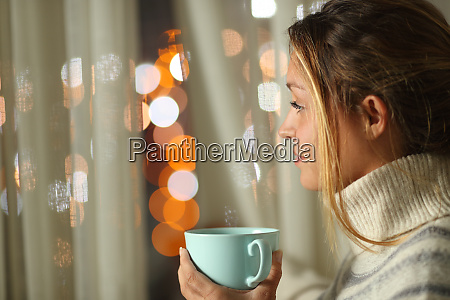woman holding coffee cup looking through