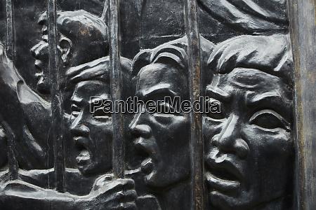 bas relief of prisoners behind bars