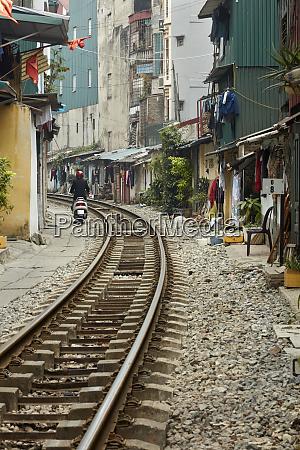 people and houses beside railway line
