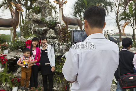 vietnam hue man photographing family with