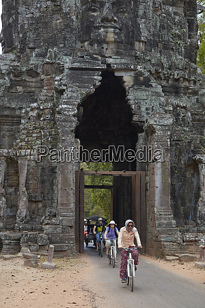 cyclists going through victory gate angkor