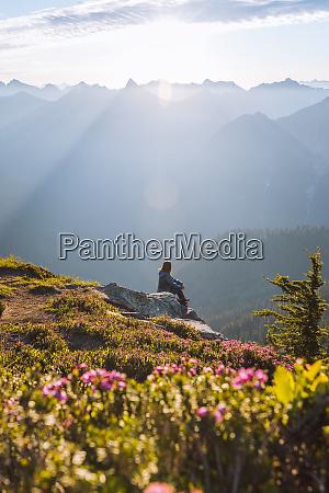 female hiker enjoying sun on peak
