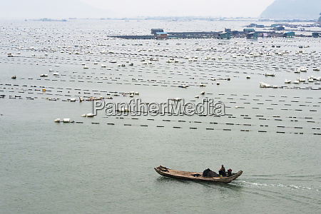 fishing boat with floating village along