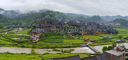 village with farmland in morning mist