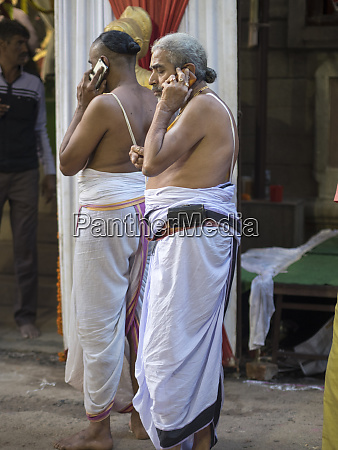 hindu priests using mobile phone in