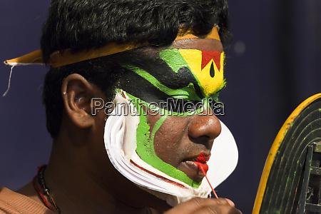 kathakali dancer applying make up kerala