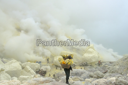 miners carrying sulfur amid sulfur gas