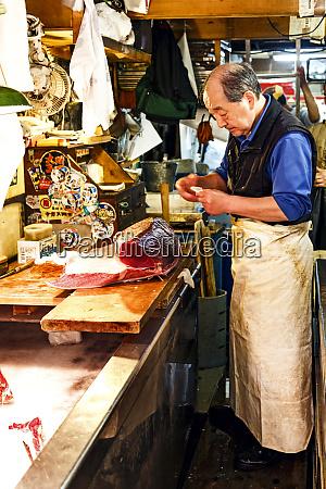 tokyo japan fish monger prepares fish