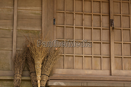 traditional straw brooms left under the