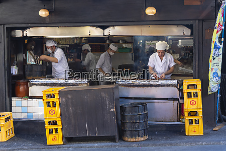 cooks preparing and cooking eel on