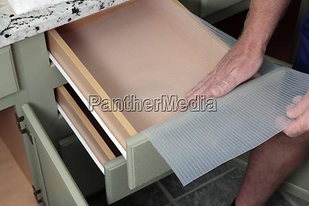 caucasian male hands placing plastic drawer