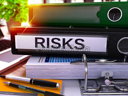 risks on black ring binder blurred