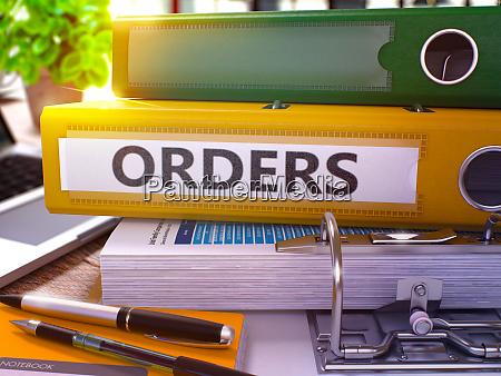 orders on yellow ring binder blurred