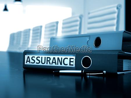 assurance on ring binder blurred image