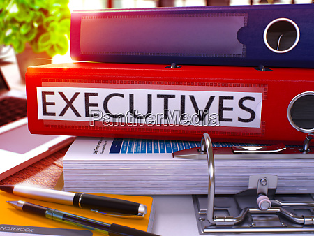 executives on red ring binder blurred