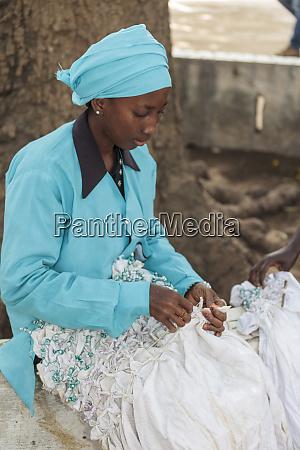 africa gambia banjul woman tying fabric