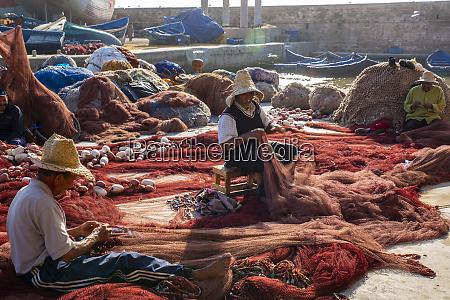 essaouira morocco fishermen repairing fish nets