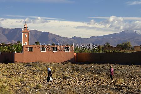 morocco skoura women passing mosque in