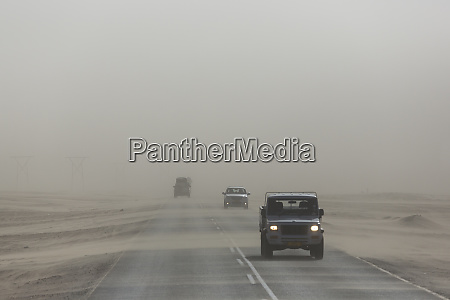 sand blows across the highway and