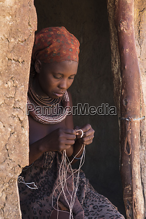 young mother weaves rope in the