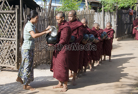 woman giving out alms food to