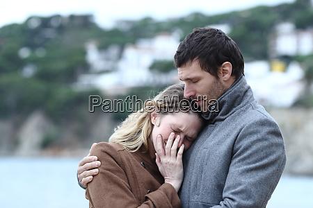 man comforting a sad woman in