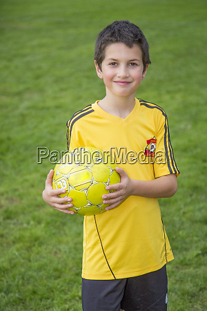 young boy plays with a soccer