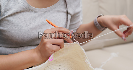 woman knitting with crochet hook and
