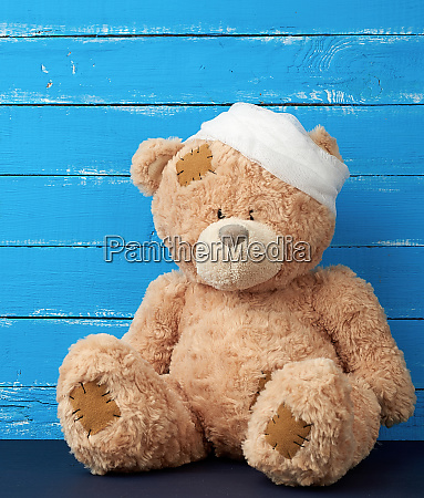 sad brown bear sits with bandaged