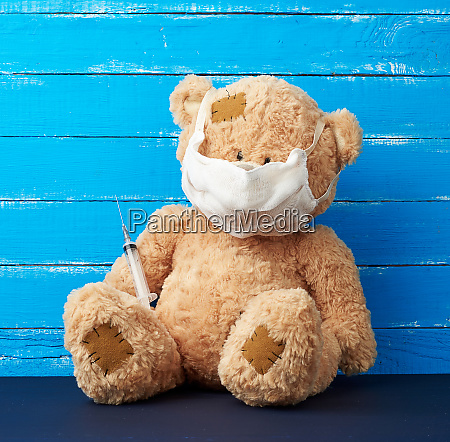 beige big teddy bear with patches