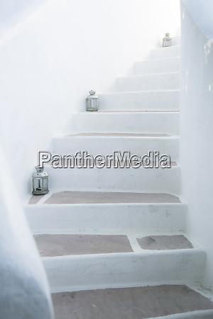 white staircase with hurricane lamps palm