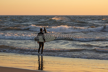 surfers on beach at sunset on