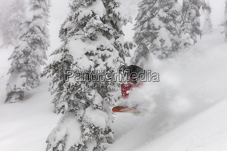 snowboarding in powder at whitefish mountain